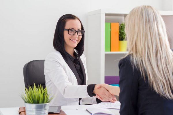 32568781 - two women shaking hands while meeting in the office
